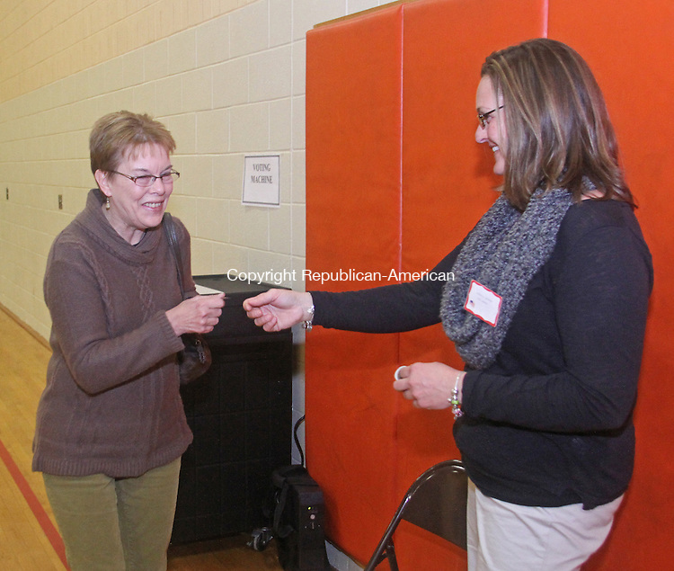 Winsted, CT-110513MK03 Linda Ives gets a sticker from Georgi Andrews after she cast her vote at the Pearson Middle School in Winsted on Tuesday night.  There were sixteen candidates running for the Winsted Board of Selectmen.  Andrews said that the turn out by the voters had been steady throughout the day . Michael Kabelka / Republican-American.