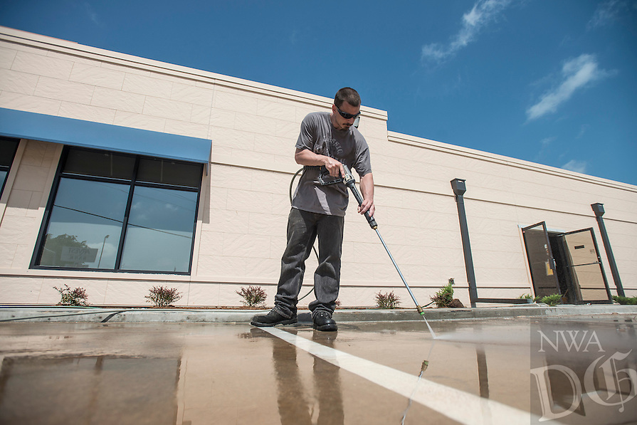 STAFF PHOTO ANTHONY REYES<br /> Rick Grissom, with C.R. Crawford Construction of Fayetteville, power washes a parking lot Monday, June 30, 2014 in Springdale. Grissom was helping to clean up the lot after the building was recently refurbished. It will house a MedExpress urgent care center.