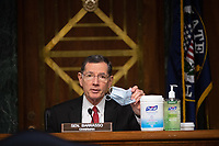 "Chairman Sen. John Brasso (R-WY) holds up a mask and shows off cleaning products at a hearing titled ""Oversight of the Environmental Protection Agency"" before the US Senate Environment and Public Works Committee in the Dirksen Senate Office Building on May 20, 2020 in Washington, DC.  EPA Administrator Andrew Wheeler will be asked about the rollback of regulations by the Environment Protection Agency since the pandemic started in March.  <br /> Credit: Kevin Dietsch / Pool via CNP/AdMedia"