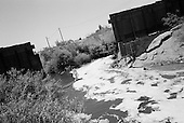 Calexico, California<br /> May 16, 2008<br /> <br /> The New River, filled with Mexican pollutants, flows swiftly north through a break in the the border fence. Many times illegal immigrants try to move into the US inside the river and the pollution.