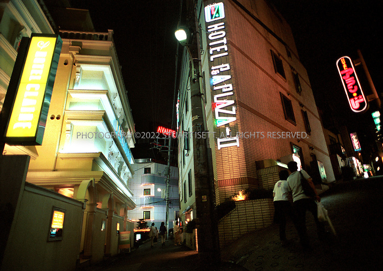7/6/01?Tokyo, Japan..A young Japanese couple duck into a  'Love Motel' in Shibuya, Tokyo's trendy youth district that has hundreds of the motels..All photographs ©2003 Stuart Isett.All rights reserved.This image may not be reproduced without expressed written permission from Stuart Isett.