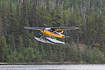 A Cessna 185 owned by Liard Air,  lifts off Mayfield Lakes having dropped off canoeists for a trip down the Gataga River.  Muskwa Kechika Management Area. Northeast British Columbia.  Rocky Mountains