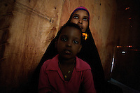 Asli Abdulle Mohammud, 28 years old, a somali refugee, holds her 10 year old daughter in her home  in the Besateen Shanty town in Aden, Yemen on Monday November the 26th 2007. Asli landed in Yemen 12 years ago arriving by boat.  her Husband died in 2003 leaving her penniless and with 4 children. she lives out of neighbors donations.///..Ever since the collapse of the Siad Barre regime in 1991 Somali men, women and children have been arriving at the port of Bosasso to buy passage in small open fishing boats to Yemen, where they are given automatic political asylum..The  boat trip, costing from 70 to 150 usd per person, can be often fatal due to the roughness of the sea, the overcrowded boats and the merciless of the smugglers..On the night of Nov 29 2007 a small fishing boat while trying to download it's load of refugees a few hundred meters from the Yemeni  shores of Meifa Haja, flipped over and was overwhelmed by the constant waves. of its 130 passengers, only 42 reached the UNHCR ( United Nations High Commissioner for Refugees )  refugee center in Meifa. 30 bodies where recovered the next day.  the rest are still unaccounted for.. UNHCR  estimates more than 80.000 somali refugees live  in the country residing mostly in shanty towns in Sana'a' and Aden.