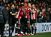 2nd December 2017, Griffen Park, Brentford, London; EFL Championship football, Brentford versus Fulham; Ollie Watkins of Brentford shoots celebrates with his players towards the Brentford fans after scoring his sides 3rd goal in the 84th minute to make it 3-1