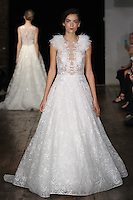 """Model walks runway in a """"L'Amour"""" bridal gown from the Alyne by Rita Vinieris Fall 2017 collection on October 7th, 2016 during New York Bridal Fashion Week."""
