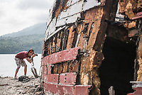 Photographer taking a photo of a shipwrecked fishing boat, Pulau Weh Island, Aceh Province, Sumatra, Indonesia