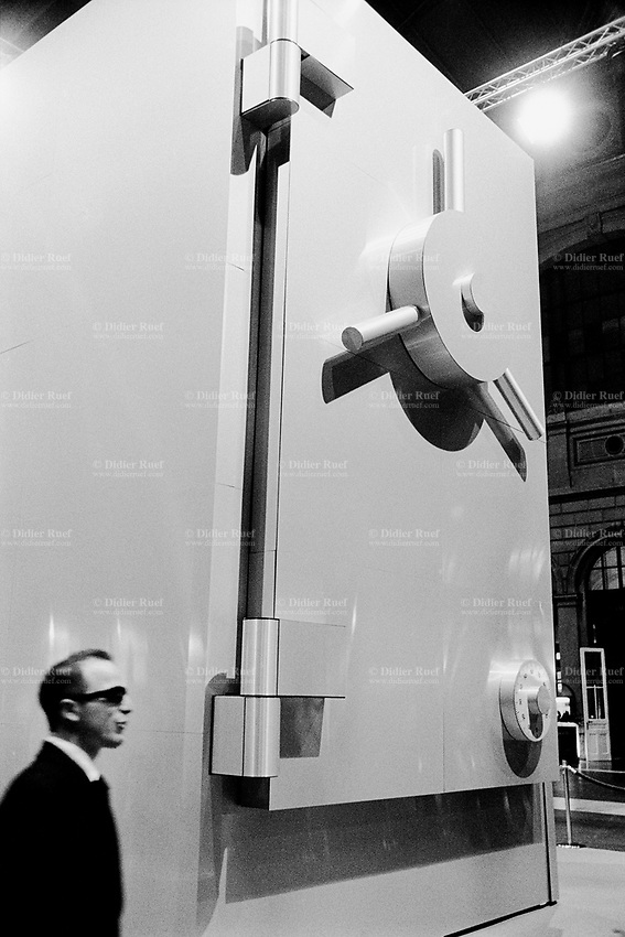 Switzerland. Canton Zürich. Zürich. Hall of the main railway station. A man, dressed with a black suit and wearing dark glasses, stands near the imitation of a giant bank safe with a vault door. © 2006 Didier Ruef