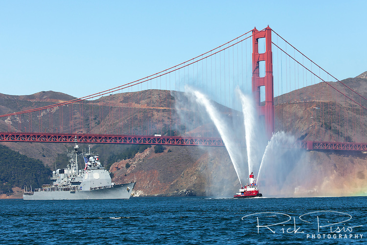 The Arleigh Burke-class guided-missile destroyer USS Ross (DDG-71) is escorted through the Golden Gate by the San Francisco Fireboaot Gaurdian #2 in October of 2015.