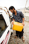 Driver, Sa'ad Ali Sohail Saeed, filling up tank with gas canister, Hawf Protected Area, Yemen