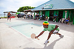 "Originating in Barbados in the 1930s, Road Tennis is played in on the back streets and roads of the country or now in permanent courts, such as the ones in Oistins and Speightstown.  The game is played on a 10x20 foot court and the ""net"" is an 8 inch by 10 foot piece of wood.  It has the same rules as table tennis (ping pong) and is a 21 point game.  It uses hand hewn rackets made largely from plywood and tennis balls that have had the fur removed.  It is the only endemic sport to Barbados and is wildly popular among the local population.  Pictured here is the road tennis court at Oistins."
