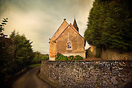 An old stone church sits on top of a stone wall right off of an old dirt road in the Loire Valley of France