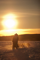 Musher and his team race into the sunrise across Devil's Track Lake during the 2011 running of the John Beargrease Sled Dog Marathon.
