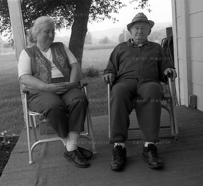 Elderly father and daughter sitting on the porch on a farm