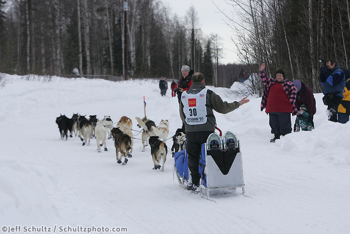 Gerald Sousa waves to crowd shortly after leavingWillow Restart .  2005 Iditarod Sled Dog Race