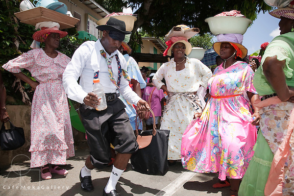 """Tobago Heritage Festival, """"National Treasures Day"""", Charlotteville - Women carry the clothes of the dead after the ceremony of washing, man dancing"""