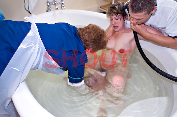 Midwife assisting the mother giving birth in a water bath. The baby is almost born and the midwife will lift the infant out of the water and hand him to his mother. This image may only be used to portray the subject in a positive manner..©shoutpictures.com..john@shoutpictures.com