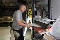 Alberto inserts a sheet of parchment into a brushing mechanical system to ligt off any blemish at the tannery factory of Scriptorium SL in Valencia, Spain. Picture by Manuel Cohen