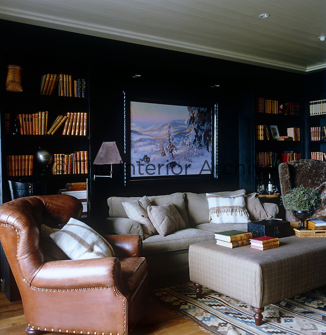 A masculine feel has been created in this library with a beige-covered sofa, antique leather armchair and shelves painted a deep black