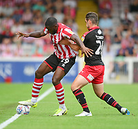 Lincoln City's John Akinde shields the ball from Swindon Town's Dion Conroy<br /> <br /> Photographer Chris Vaughan/CameraSport<br /> <br /> The EFL Sky Bet League Two - Lincoln City v Swindon Town - Saturday 11th August 2018 - Sincil Bank - Lincoln<br /> <br /> World Copyright &copy; 2018 CameraSport. All rights reserved. 43 Linden Ave. Countesthorpe. Leicester. England. LE8 5PG - Tel: +44 (0) 116 277 4147 - admin@camerasport.com - www.camerasport.com