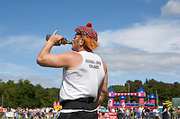 A competitor drinks a bottle of beer at the Helensburgh and Lomond Highland Games in Argyll.