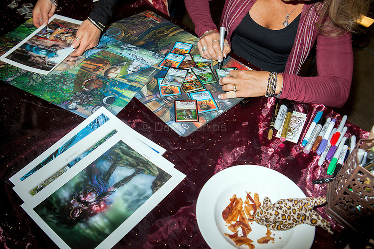 Terese Nielsen autographs fans' Magic cards illustrated with her artwork , which she began contributing to the game about twenty years ago. The company has commissioned hundreds of artists over there years as new sets are released. <br /> <br /> Danny Ghitis for Bloomberg Businessweek