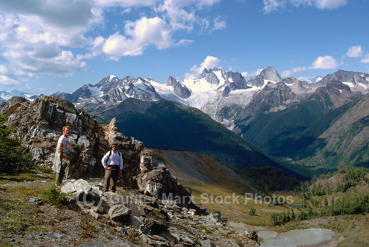 Bugaboo Provincial Park, BC, British Columbia, Canada - Male Hikers hiking in Alpine Region of Purcell Mountains - Bugaboo Glacier and Marmalota Peak in center background