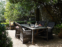 A stone faux-bois table flanked by a group of wicker garden chairs is placed in the shade of a tree in the garden