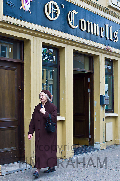 Elderly woman strolls past O'Connells bar in Charleville, County Cork