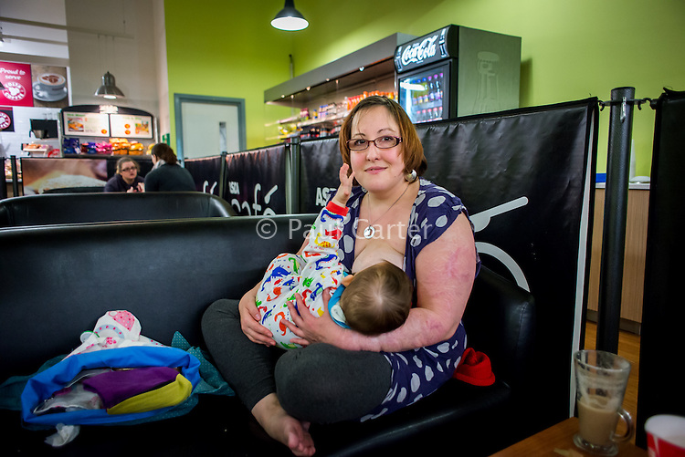 A young woman happily breastfeeding her 11 month old baby in a supermarket cafe.<br /> <br /> Image from the &quot;We Do It In Public&quot; documentary photography project collection: <br />  www.breastfeedinginpublic.co.uk<br /> <br /> Dorset, England, UK<br /> 11/04/2013<br /> <br /> Photo &copy; Paul Carter / WDIIP.co.uk