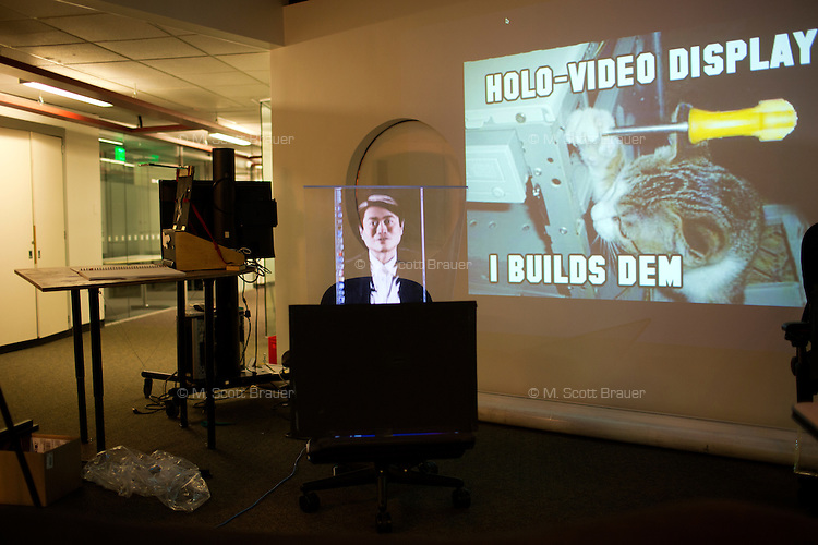 A reflected hologram of MIT Media Lab director Joi Ito is on display next to a cat meme in a Media Lab hallway at MIT in Cambridge, Massachusetts, USA.