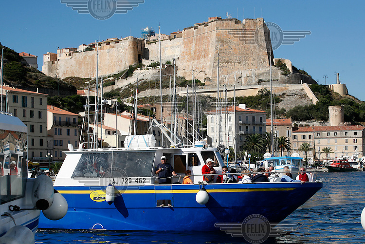 Tourist boat in the marina below  the old town of Bonifacio, also called the Citadel. The historic town is a popular tourist destination. Corsica..© Fredrik Naumann / Felix Features Corsica is a French island in the Mediterranean Sea. It is located west of Italy, southeast of the French mainland, and north of the Italian island of Sardinia. Mountains make up two-thirds of the island, forming a single chain. (Wikipedia)
