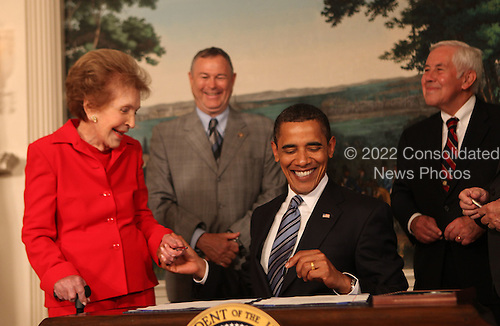 Washington, DC - June 2, 2009 -- United States President Barack Obama gives former first lady Nancy Reagan a ceremonial pen at the signing of the Ronald Reagan Centennial Commission Act in the Diplomatic Reception Room of the White House on Tuesday, June 2, 2009 .  In the background at left is U.S. Representative Dana Rohrabacher (Republican of California) and U.S. Senator Richard Lugar (Republican of Indiana). <br /> Credit: Dennis Brack / Pool via CNP