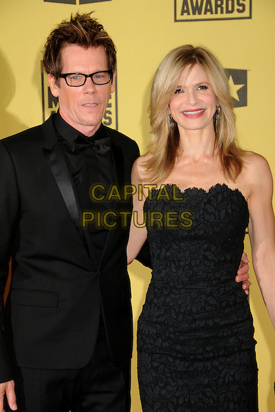 KEVIN BACON & KYRA SEDGWICK.15th Annual Critics' Choice Movie Awards - Arrivals held at the Hollywood Palladium, Hollywood, California, USA, 15th January 2010..half length black strapless dress bow tie glasses married couple husband wife pattern tuxedo tux print .CAP/ADM/BP.©Byron Purvis/Admedia/Capital Pictures