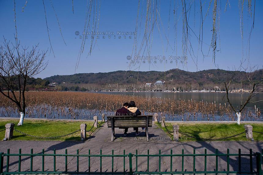 Una giovane coppia seduta in una panchina del lungo lago dell'Ovest.<br /> A young couple sitting on a bench at the West Lake