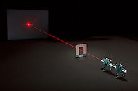 DIFFRACTION OF LASER LIGHT ON SINGLE HUMAN HAIR<br /> A Laser is Used to Determine Width of Human Hair.<br /> A laser pointer is used to project a laser beam that is diffracted around a single human hair mounted to a cardboard frame. Both the laser pointer and the frame that holds the laser are supported by binder clips.