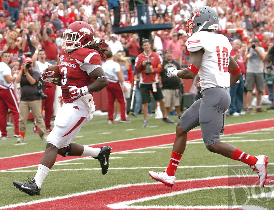 NWA Media/ANDY SHUPE - Arkansas running back Alex Collins scores ahead of Nicholls defensive back Josh Dewey (10) during the first quarter Saturday, Sept. 6, 2014, at Razorback Stadium in Fayetteville