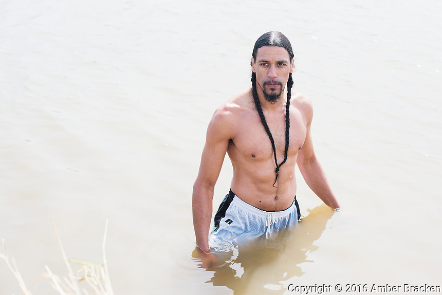 """Amawon Weeden, of the Mashpeewampanoag, or Great Water People of the First Light, in the Cannonball River at Sacred Stone Camp on Saturday, September 10, 2016. """"Water is our identity, it's who we are,"""" says Weeden. He says he couldn't stand by and watch indigenous people be victimized without doing something to help."""