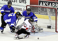 University of Nebraska Omaha's Zahn Raubenheimer looks to get control of a loose puck in front of Alabama-Huntsville goalie Clarke Saunders during the third period. UNO beat Alabama-Huntsville 4-0 Friday night at Qwest Center Omaha.  (Photo by Michelle Bishop)