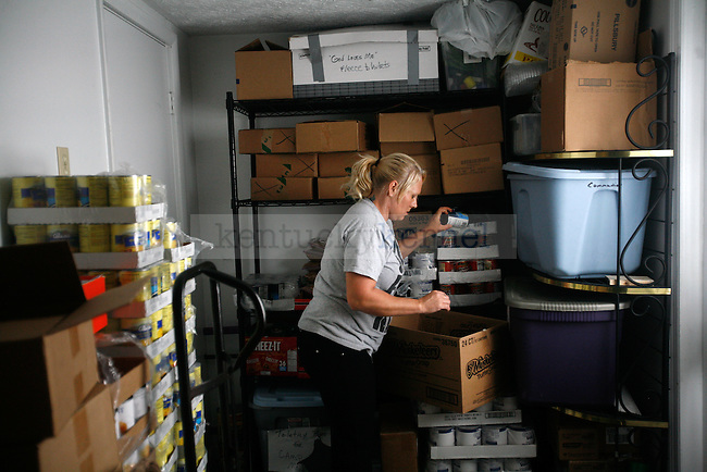 Missy prepares a box of food and hygiene products for a local family in need. If Missy knows the family, she makes sure there is enough for everyone included in the box. Photo by Adam Wolffbrandt