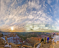 In this broad panorama of Lipan Point on the Grand Canyon's south rim, the tourists can't look directly at the bright sunset-lit clouds arching over them.