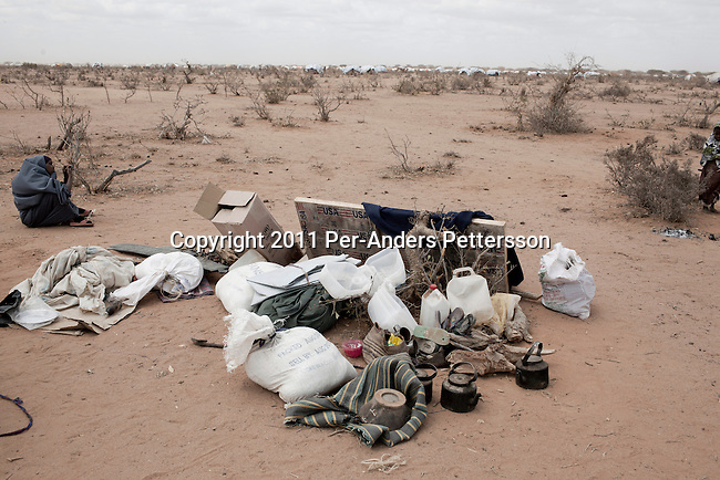 DADAAB, KENYA - JULY 30: Newly arrived refugees with their belongings outside the IFOR refugee camp on July 30, 2011 outside Dadaab, Kenya. Hundreds of thousands of people have fled the hardship and civil war in Somalia to Dadaab. A severe drought has added to the misery and hardship. Some refugees has walked for up to thirty days to reach the camp, and some children died on the way, due to lack of food and water. (Photo by Per-Anders Pettersson)