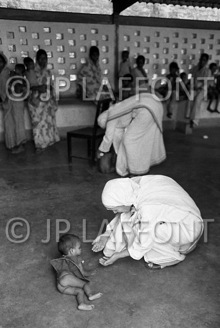 "January 1976, Calcutta, India --- Mother Teresa bends down to play with an infant lying on the floor. The first Home for the Dying opened in 1952 and was a free hospice for the poor. Mother Teresa (Agnes Gonxha Boyaxihu) the Roman Catholic, Albanian nun revered as India's ""Saint of the Slums"", was awarded the 1979 Nobel Peace Prize. --- Image by © JP Laffont"