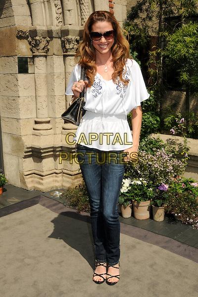 SHANNON ELIZABETH.Lloyd Klein Couture Fall 2010 Presentation held at Lloyd Klein House of Couture, Los Angeles, California, USA, 24th  March 2010.. full length white top jeans bag black sandals  shirred waist blue embroidered sunglasses  elasticated .CAP/ADM/BP.©Byron Purvis/AdMedia/Capital Pictures.