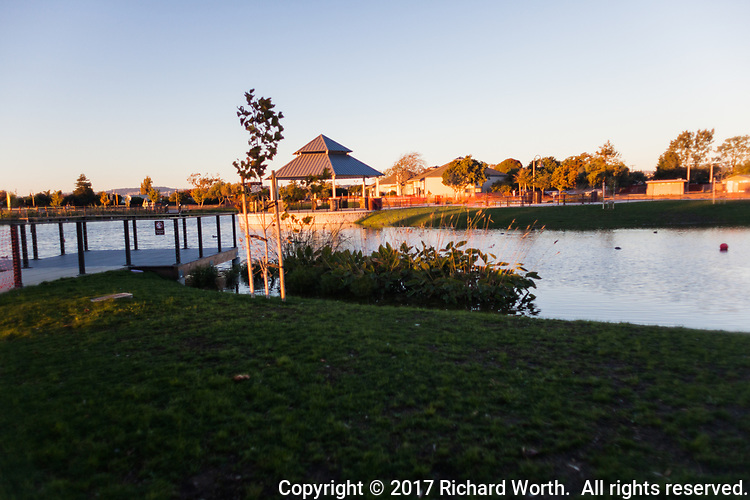 Cast in sunset glow, the gazeebo presiding over the pond's waters.
