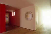 A red wall is a focus in the interior of this minimalist entrance hall