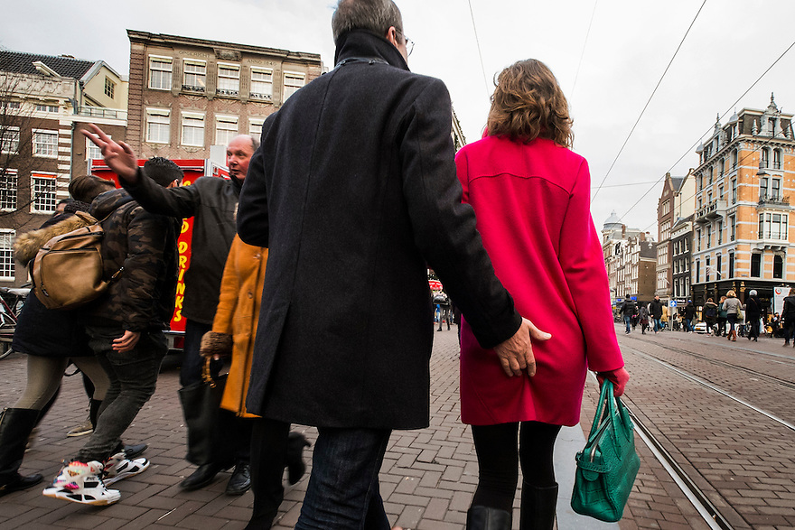 Nederland, Amsterdam, 13 dec 2014<br /> Een man kan niet van de billen afblijven van zijn vriendin (of vrouw). Tijdens het lopen betast hij haar meer dan onopvallend.<br /> Foto: (c) Michiel Wijnbergh