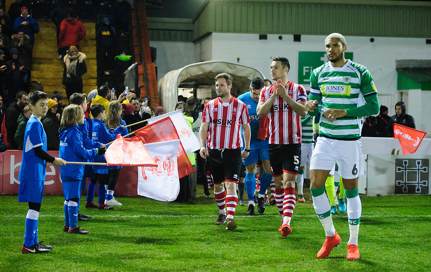 30-year-old Alex Newbold walks out onto the pitch with Lincoln City's Jason Shackell after being made one of the mascots for the evening as a surprise during his stag do<br /> <br /> Photographer Chris Vaughan/CameraSport<br /> <br /> The EFL Sky Bet League Two - Lincoln City v Yeovil Town - Friday 8th March 2019 - Sincil Bank - Lincoln<br /> <br /> World Copyright © 2019 CameraSport. All rights reserved. 43 Linden Ave. Countesthorpe. Leicester. England. LE8 5PG - Tel: +44 (0) 116 277 4147 - admin@camerasport.com - www.camerasport.com