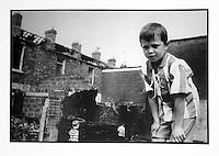 Irlanda del Nord, Belfast , Northern Ireland, Irlande du Nord, un ragazzo con maglia a righe osserva, sullo sfondo un quartoere popolare durante gli scontri