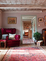Cheerful Turkish rugs cover the wooden floorboards throughout the house. In the dusky pink library a substantial velvet, wing-backed chair stands in a corner