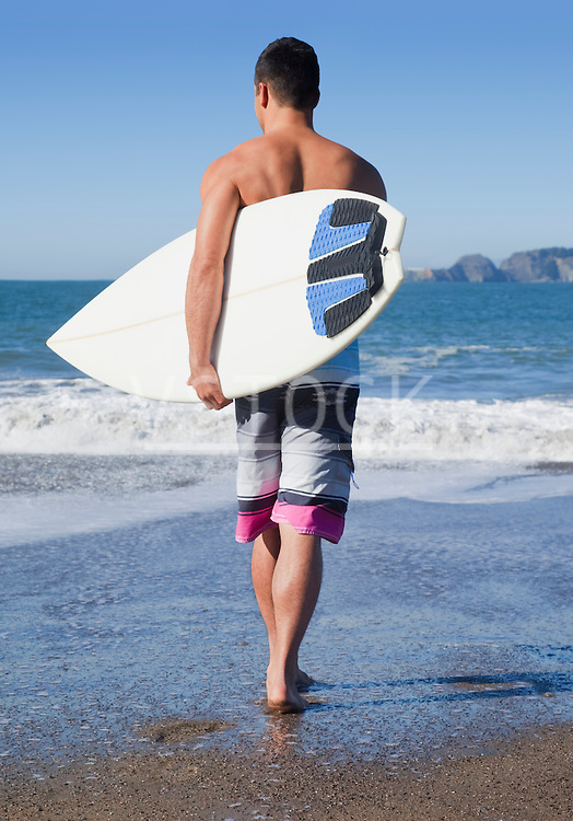 USA, California, San Francisco, man carrying surfboard on Baker Beach